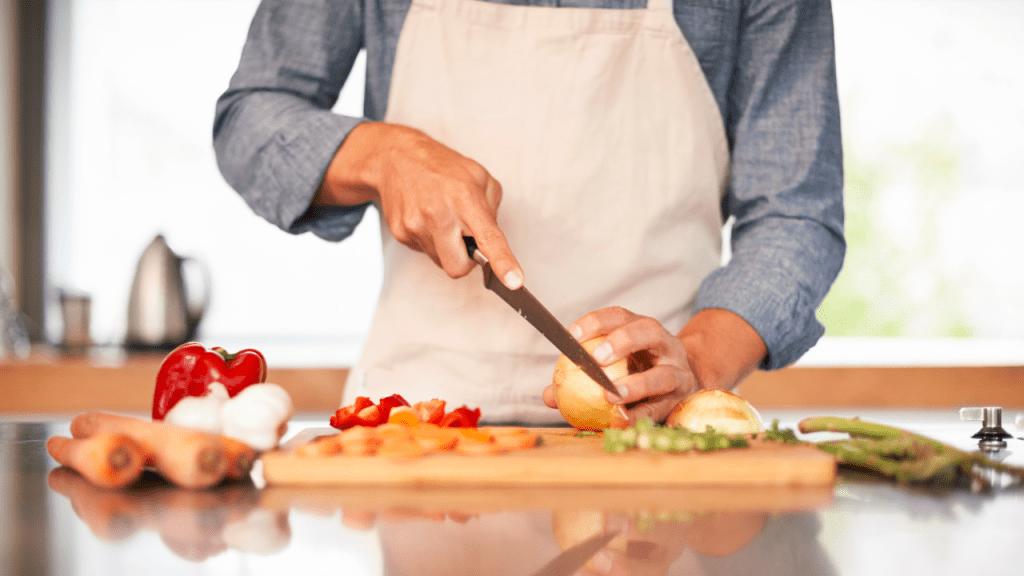 person slicing vegetable ingredients