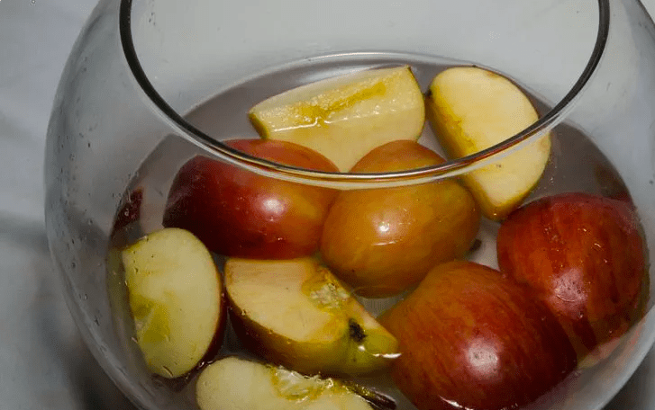 water and apples in jar