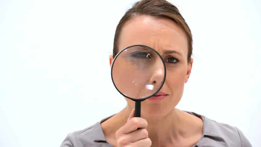 woman looking curiously with a magnifying glass