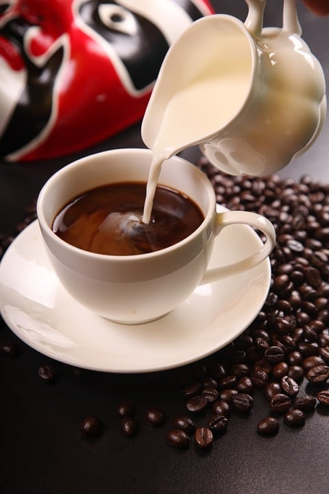 a cup of coffee in a plate with coffee beans