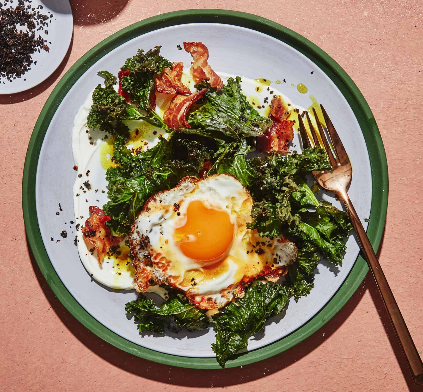 a plate of turmeric fried egg and bacon with kale