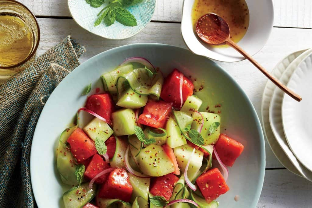 a salad bowl of watermelon, cucumber and honeydew with honey